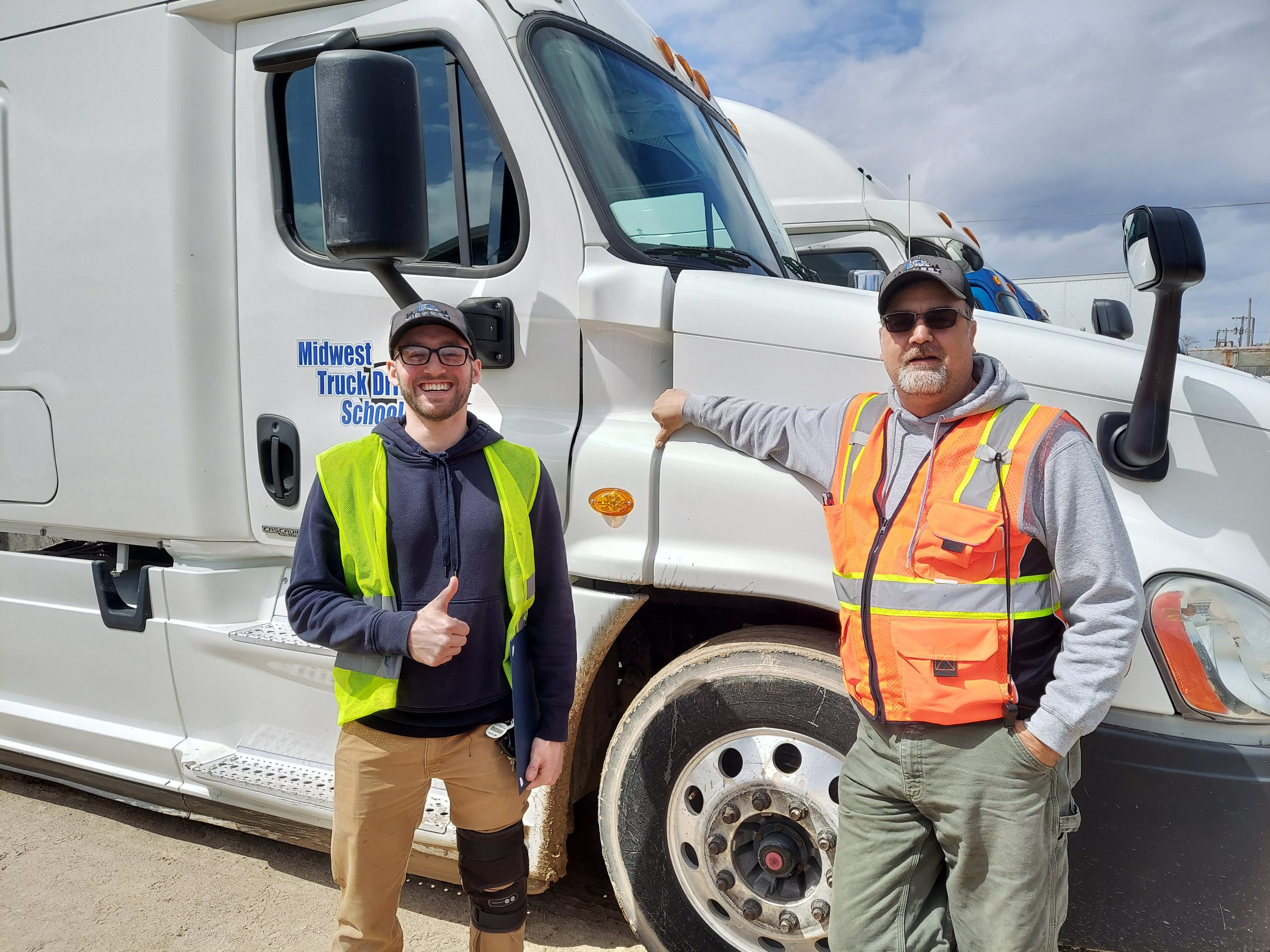Jacob and his trainer stand in front of a Midwest Truck Driving School truck.