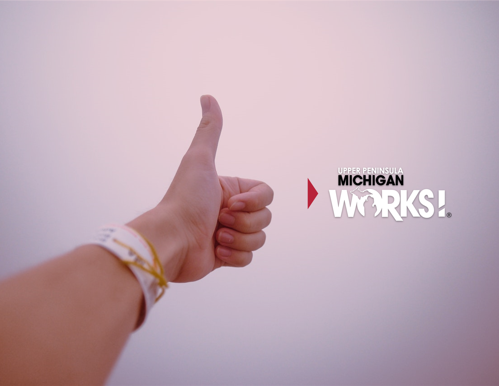 A person gives a thumbs up with the UP Michigan Works logo overlayed.