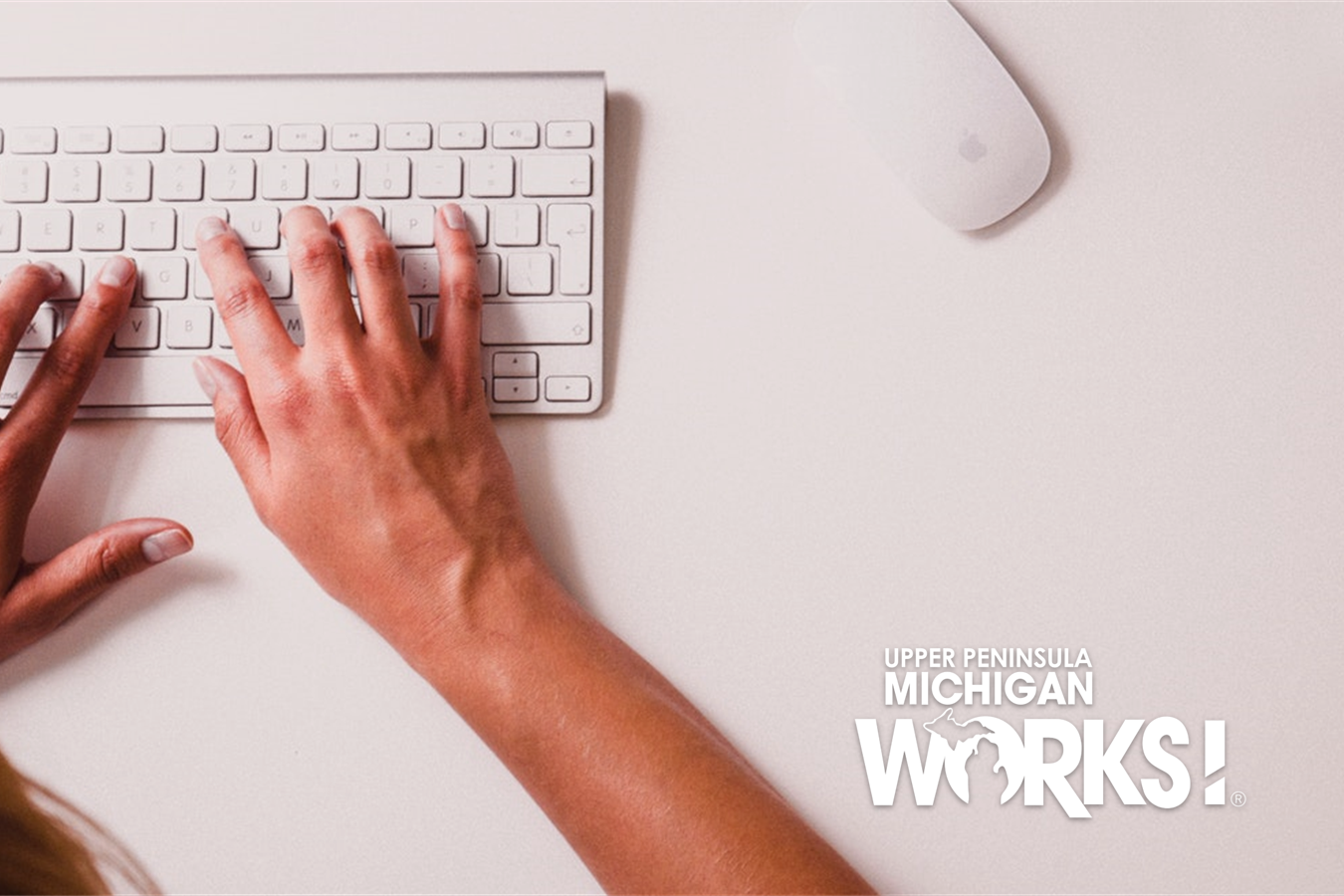 Hands are typing on a white keyboard.