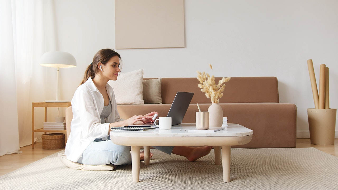 A woman is working on a laptop while sitting on her living room floor.