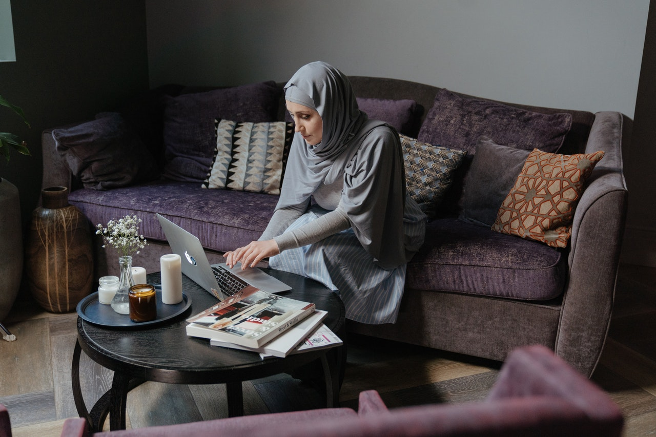 A woman sits on a couch and uses a laptop on her coffee table.